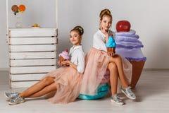Tiener modeltweelingenzusters met buitensporige cakes royalty-vrije stock afbeeldingen