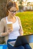 Tiener in oogglazen met laptop en koffie Stock Foto's