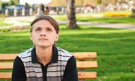 Tiener op de bank in het park Stock Afbeelding