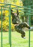 Tiener op klimrek in relais Stock Foto's