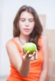 Tiener in oranje t-shirt die een groene appel tonen Stock Foto's