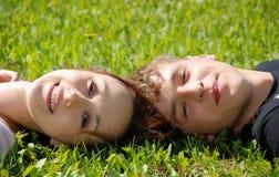 tiener paar dat op het gras legt Stock Foto's