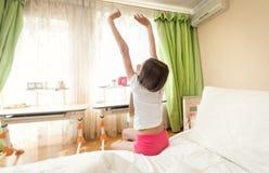 Tiener in pyjama's die zich op bed bij ochtend uitrekken royalty-vrije stock foto's
