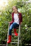 Tiener in rode gumboots die op ladder bij appeltuin stellen Royalty-vrije Stock Afbeelding