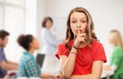 Tiener in rode t-shirt met vinger op lippen stock foto