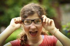 Tiener shortsighted meisje die met bijziendheid de nieuwe glazen van de gezichtscorrectie dragen stock foto's