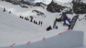 Tiener snowboarder rit op springplank zonnig Karton kosmische voorwerpen Mensen stock video