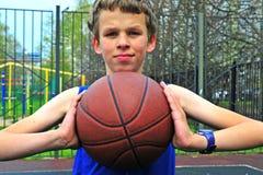 Tiener speelbasketbal op het hof Stock Foto