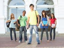 Tiener Studenten die zich buiten de Bouw van de Universiteit bevinden stock foto