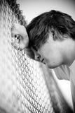 Tiener tegen omheining stock afbeelding