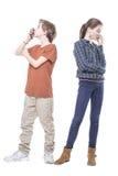Tiener twee die hun slimme telefoons kussen stock fotografie