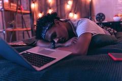 Tiener van het hebben van pret en het vallen van in slaap recht dat de hele dag naast laptop wordt vermoeid royalty-vrije stock fotografie