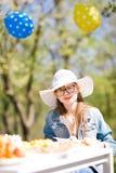 Tiener verouderd meisje in witte sunhatzitting door lijst aangaande verjaardag Gard royalty-vrije stock fotografie
