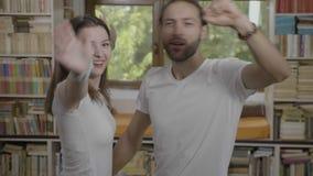 Tiener vrolijke paar het luisteren muziek en het dansen thuis doend grappige funky bewegingen - stock footage