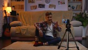 Tienerblogger die nieuwe video op smartphone voor zijn aanhangers registreren, hobby stock videobeelden