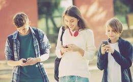 Tienerjaren die met mobiele telefoons begraven Stock Afbeelding