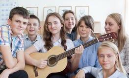 tienerjaren die pret en het spelen van gitaar en het zingen hebben Stock Fotografie