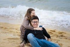 Tienerjaren die pret hebben bij het strand Stock Afbeelding