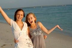 Tienerjaren die pret hebben bij strand Stock Foto