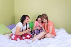 Tienerjaren die tekstberichten lezen Stock Fotografie