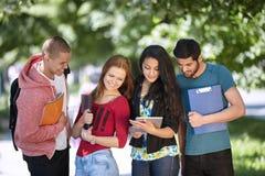 Tienerjaren die uit buiten school hangen Stock Afbeelding