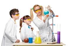 Tienerjaren en leraar van chemie bij les het maken stock afbeeldingen