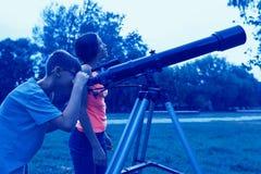Tienerjaren met een telescoop in de avond Kinderen die met rente in de hemel kijken royalty-vrije stock afbeeldingen