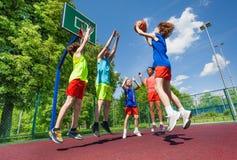 Tienerjarensprong voor bal tijdens basketbalspel Stock Afbeeldingen