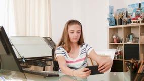Tienerjong geitje die dwaze gezichten maken aan de camera op haar smartphone stock videobeelden