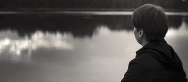 Tienerjongen die aan water in melancholische stemming kijken stock afbeelding