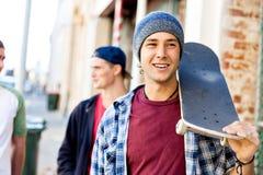 Tienerjongen die bij de straat met zijn skateboard lopen stock foto's