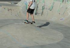 Tienerjongen die in een sportenpark met een skateboard rijden Royalty-vrije Stock Foto's