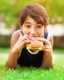 Tienerjongen die hamburger in openlucht eten Stock Fotografie