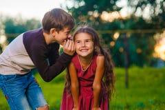 Tienerjongen die het oor van het geheime kind van het roddelmeisje fluisteren stock foto