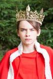 Tienerjongen die kroon waarnemende koning dragen stock afbeeldingen