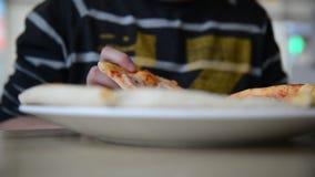 Tienerjongen die pizza in koffie eten stock video