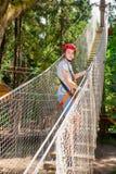Tienerjongen die veiligheidsmateriaal dragen die een kabelscursus in een treetop avonturenpark ingaan royalty-vrije stock fotografie