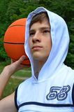 Tienerjongen in een kap en in een wit overhemd met een bal voor basketbal stock foto
