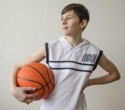 Tienerjongen in een wit overhemd met een bal voor basketbal royalty-vrije stock afbeelding