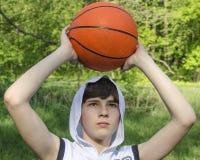 Tienerjongen in een wit overhemd met een bal voor basketbal stock fotografie