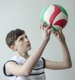 Tienerjongen in een wit overhemd zonder kokers met een bal voor volleyball Stock Foto's