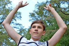 Tienerjongen in een wit overhemd zonder kokers met handen uitgestrekt in een gebaar van overwinning stock afbeelding