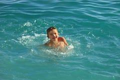 Tienerjongen het baden in het overzees of de oceaan warme zonnige dag Royalty-vrije Stock Fotografie