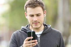 Tienerjongen het luisteren muziek met earbuds stock fotografie