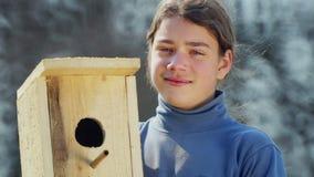 Tienerjongen met een vogelhuis voor vogels stock footage