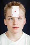 Tienerjongen met Speelkaart aan Voorhoofd wordt geplakt dat Royalty-vrije Stock Afbeelding
