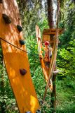 Tienerjongen op een kabelscursus in een treetop avonturenpark die de hangende hindernis van de kabelbrug overgaan stock afbeelding