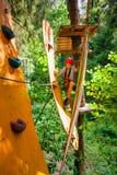 Tienerjongen op een kabelscursus in een treetop avonturenpark die hangende kabelhindernis overgaan stock afbeeldingen