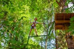 Tienerjongen op een kabelscursus in een treetop avonturenpark die hangende kabelhindernis overgaan stock foto's