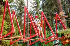 Tienerjongen op een kabelscursus in een treetop avonturenpark die hangende kabelhindernis overgaan royalty-vrije stock foto's